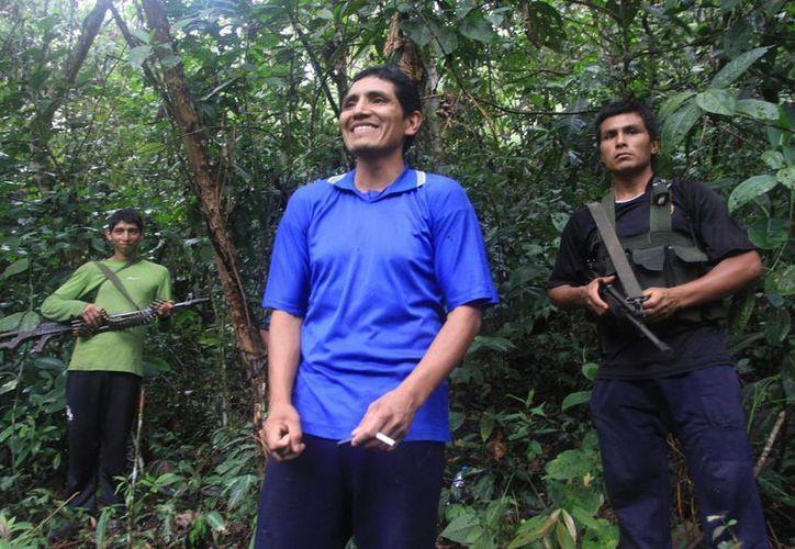 """Marco Antonio Quispe Palomino, alias """"Gabriel"""" (c), sonriendo acompañado de dos miembros de Sendero Luminoso en medio de la selva de la región Cusco. (EFE/Archivo)"""
