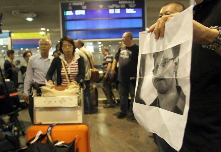 Periodistas muestran una imagen de Edward Snowden a los pasajeros que viajaron en el vuelo SU213 de Aeroflot desde Hong Kong para intentar localizarlo en el aeropuerto de Moscú. (EFE)