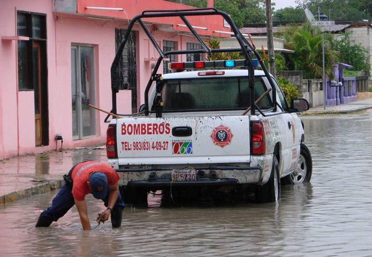 Los empleados de la Dirección de Servicios Públicos como podían quitaban la basura de los pozos de absorción. (Manuel Salazar/SIPSE)