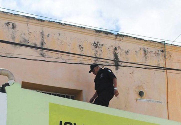 Los ladrones entraron por una ventana en techo del local. En la imagen, un agente investigando el área. (Milenio Novedades)