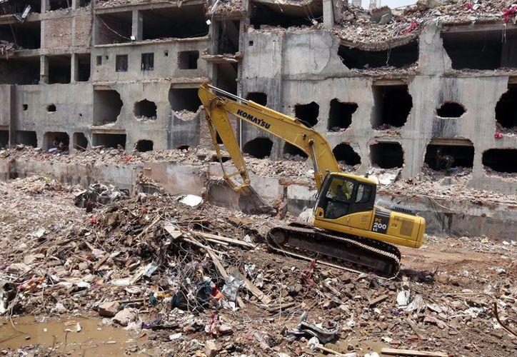 Una grúa limpia los escombros de la fábrica textil derrumbada en la localidad de Dacca. (Archivo/EFE)