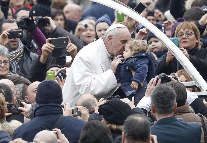 El papa Francico besa a un niño a su llegada a la primera audiencia general jubilar, celebrada este sábado en la plaza de San Pedro. (EFE)