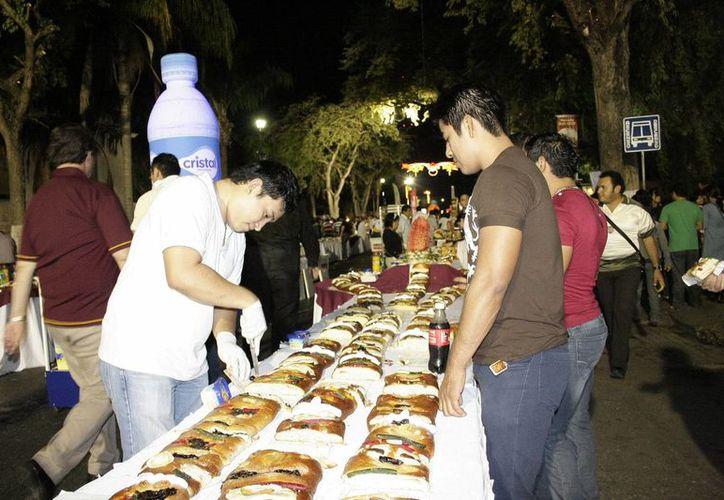 La rosca de reyes que se ofrece en Paseo de Montejo cumple 20 años el próximo 5 de enero. Imagen del evento del años pasado en donde un cliente espera que le sirvan su pedazo de pan. (Milenio Novedades)