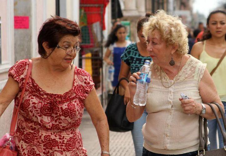 En Yucatán se utiliza una terapia innovadora para tratar los dos cánceres más agresivos que existen. En la imagen dos mujeres caminan por las calles de Mérida. (César González/SIPSE)