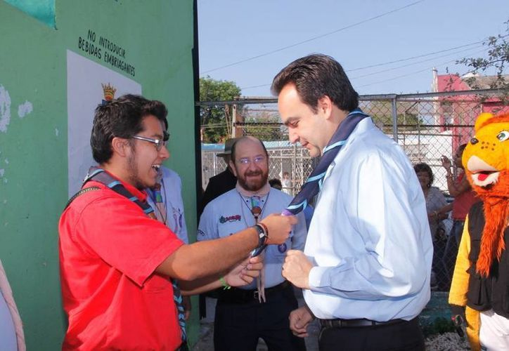 El scout Diego González, titular de la Sedesol Yucatán por un día, coloca a Nerio Torres una pañoleta escultista. (Cortesía)