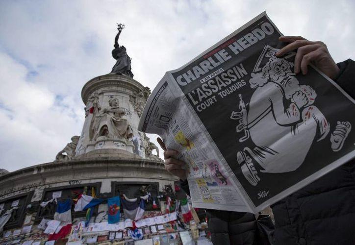 """Un hombre ojea el número especial publicado por el semanario satírico """"Charlie Hebdo"""" con motivo del primer aniversario del atentado yihadista contra su redacción, en la Plaza de la República de París. (EFE)"""