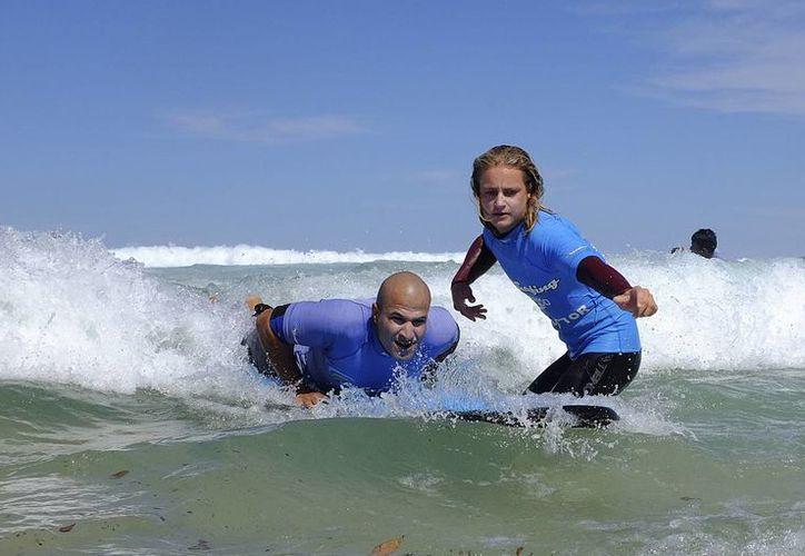 El refugiado Amín aprende a controlar una tabla de surf junto al instructor Conrad Pattinson en la playa Bondi Beach de Sydney. (Agencias)