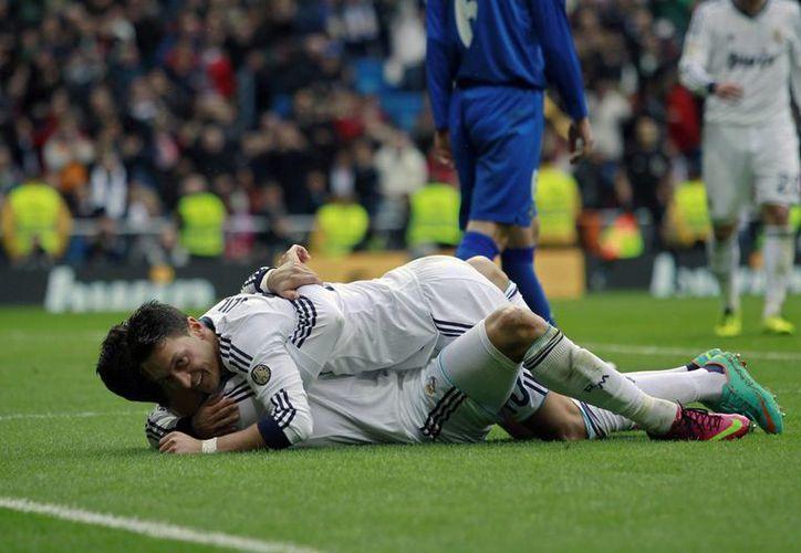 Cristiano Ronaldo, luego de uno de sus 3 goles, recibe la felicitación de Mesut Ozil. (Agencias)