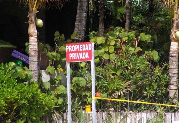 Con un cartel se advierte a los bañistas que una zona de la playa ahora ya no es pública.  (Octavio Martínez/SIPSE)