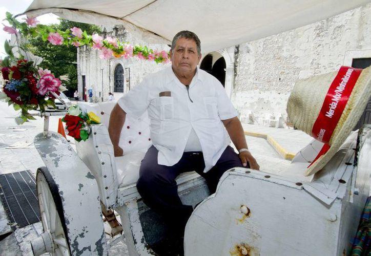 Julio Molina Sosa en espera de clientes en su coche de caballo. (Notimex)