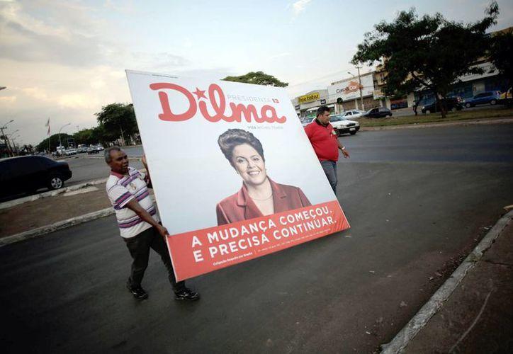 Los partidarios de Dilma Rousseff caminan con un gran cartel con la imagen de la presidenta de Brasil, que va por un segundo mandato. (Agencias)