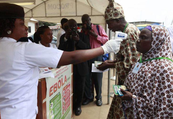 Una enfermera escanea con un  termómetro a una mujer musulmana antes de abordar un avión en el Aeropuerto Internacional de Lagos, Nigeria, en un esfuerzo por contener la propagación del virus del ébola. (Foto: AP/Sunday Alamba)