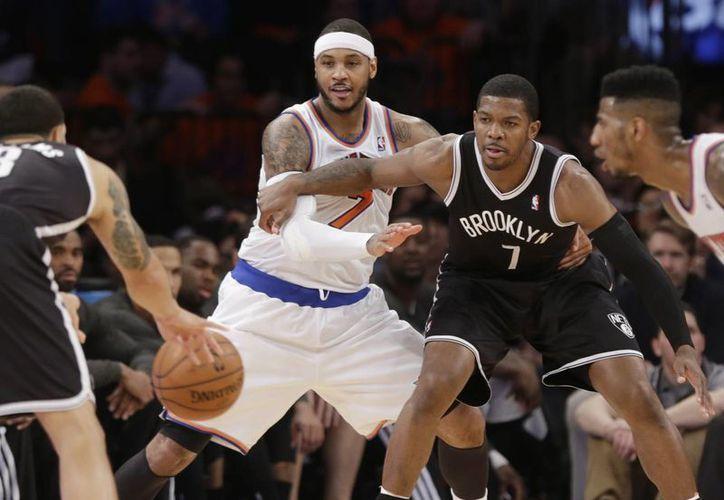 Carmelo Anthony (7) y Joe Johnson (7), de Brooklyn, pelean por la posición del balón en el partido de la NBA. (Agencias)