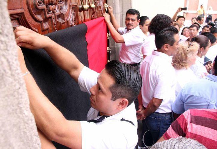 Trabajadores afiliados a la Autamuady colocan banderas rojinegras de huelga en la puerta principal del edificio central de la Uady. (José Acosta/SIPSE)