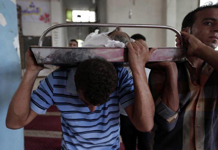 Dos palestinos cargan el cadáver de un niños muerto durante el ataque de Israel a Gaza este domingo, en Beit Lahiya. (Foto:  AP/Lefteris Pitarakis)