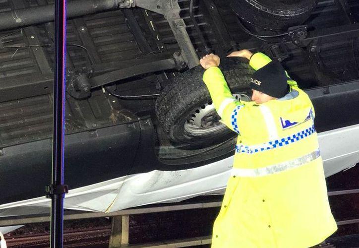 El heroico policía agarró una de las ruedas del vehículo y evitó que cayera del puente. (Foto: Twitter)