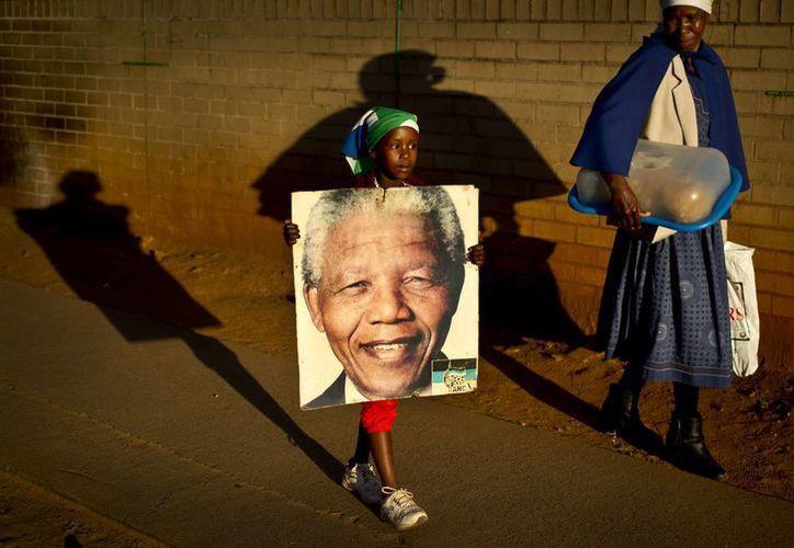Una niña sostiene un retrato de Nelson Mandela mientras ella y su abuela caminan tras haber dejado flores a la entrada del hospital donde se encuentra Mandela. (Agencias)