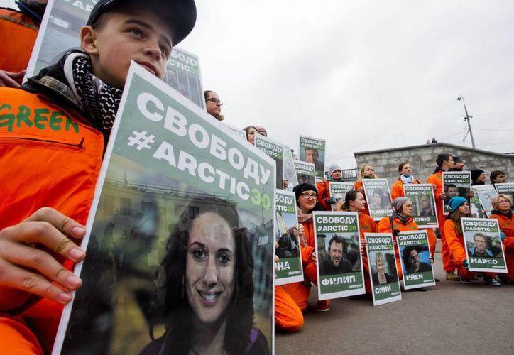 Activistas de Greenpeace portan fotos de los detenidos. (Agencias)