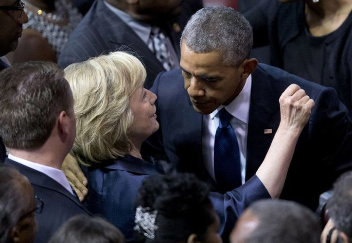 El discurso de Obama estuvo lleno de elogios al ministerio de Clementa Pinckney y arrancó los aplausos de los miles de asistentes al funeral. En la imagen, el mandatario saluda a Hillary Clinton. (AP)