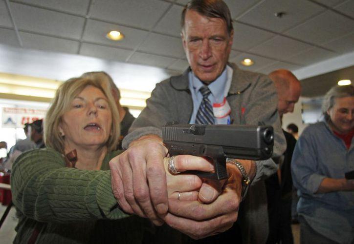 Christine Caldwell recibe entrenamiento con un revólver Glock de 9mm de un instructor de defensa persona, Jim McCarthy. (Agencias)