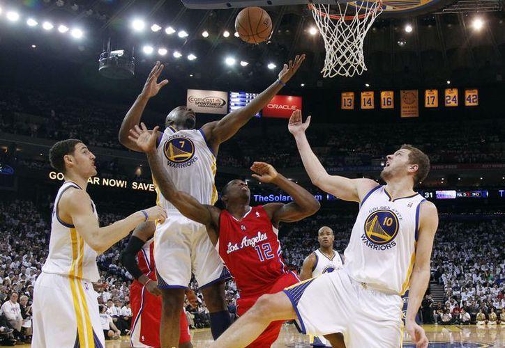 Carl Landry (7), de los Guerreros de Golden State, toma un rebote en el juego de su equipo contra los Clippers de Los Angeles. (Agencias)