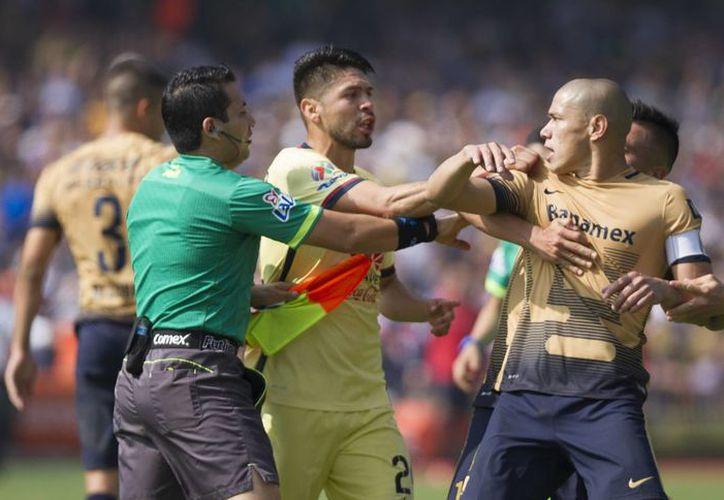 """La Conapred ya investiga la presunta agresión verbal del capitán de los Pumas, Dario Verón (derecha) en contra del Americanista Darwin Quintero en el partido de vuelta de la semifinal. El universitario le habría dicho """"simio"""" al azulcrema.- (Notimex)"""
