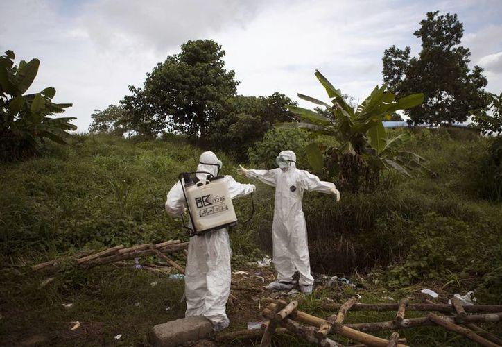 Trabajadores de salud se rocían con desinfectante después de trabajar en el interior de un depósito de cadáveres de personas sospechosas de morir de ébola en Kenema, Sierra Leona. (Agencias)