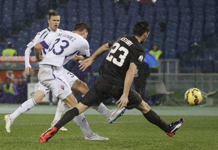 Mario Gómez al momento de 'jalar del gatillo' para anotar uno de sus goles con Fioretina ante Roma en la Copa de Italia. (Foto: AP)