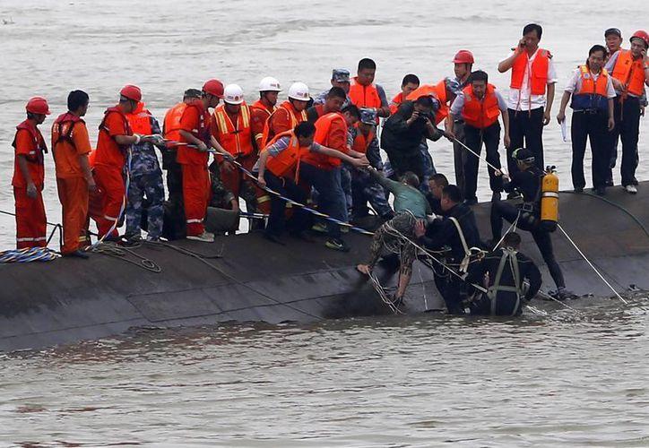 Miembros de los servicios de rescate ayudan a un superviviente tras el naufragio de un barco en el río Yangtsé en Jianli, China. El naufragio ocurrió anoche, cuando el crucero Estrella de Oriente quedó atrapado en una tormenta. (EFE)