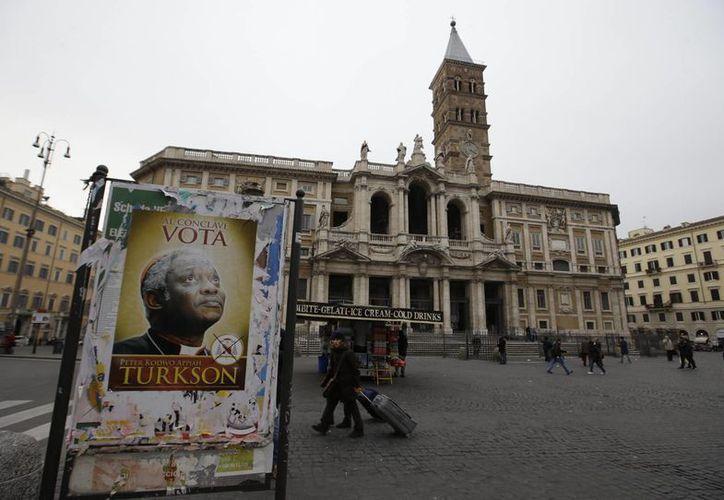 Uno de los carteles que invita a votar  por el cardenal Peter Kodwo Appiah Turkson para ser electo Papa, en la capital iItaliana. (AP)