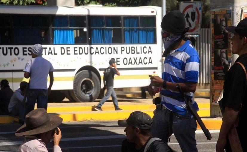 Cerca de mil 500 policías federales y estatales resguardaron la entrada principal del Ieepo ante la llegada de docentes que llegan a registrarse. Imagen de una protesta de maestros del municipio de Santo Domingo Teojomulco, en las puertas de la dependencia en Oaxaca. (Archivo/Notimex)