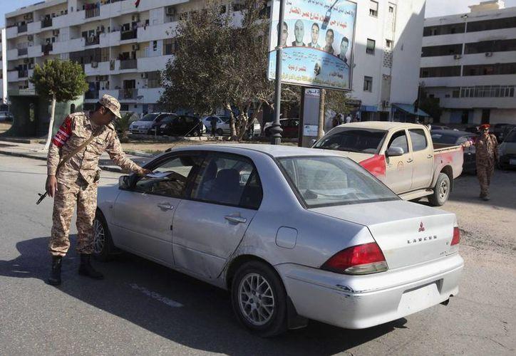 Un policía militar libio revisa la documentación del conductor de un vehículo en un punto de control establecido en una calle de Trípoli, capital de Libia, ciudad donde este viernes hubo una toma de rehenes en el consulado de Túnez. (EFE/Archivo)