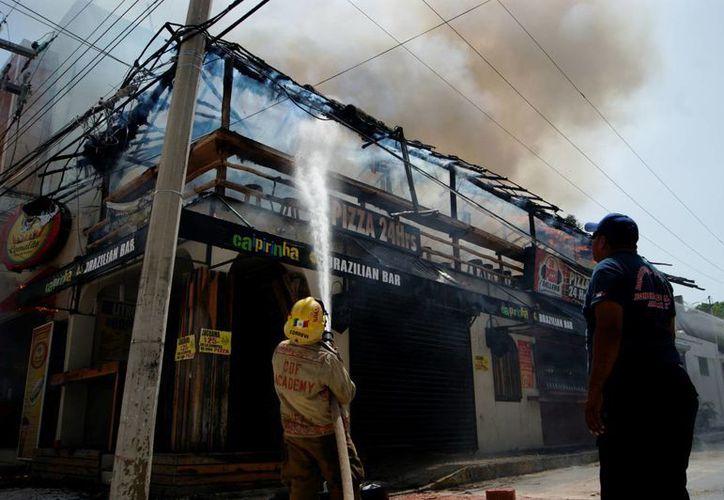 """Expertos sugieren que los dueños de palapas apliquen a sus estructuras sustancias """"retardantes"""" para evitar que sean consumidas por un incendio.  (Octavio Martínez/SIPSE)"""