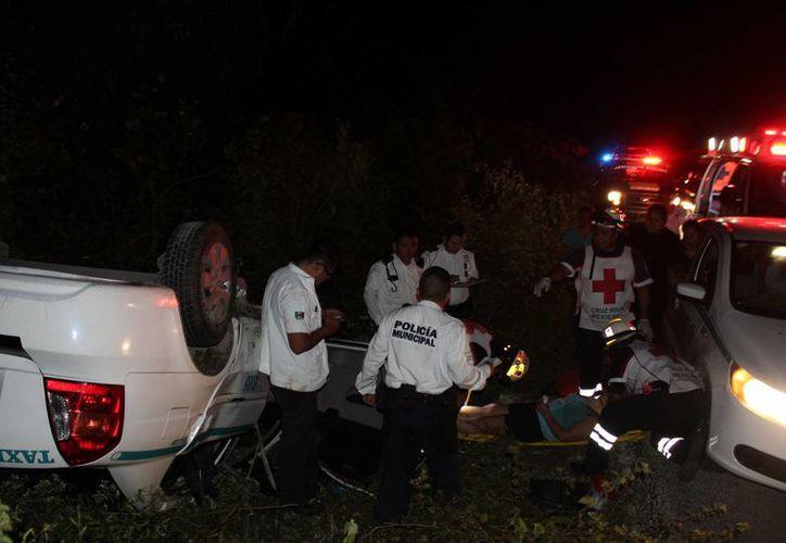 Un taxista volcó su unidad cuando esquivó a una familia que viajaba en triciclo, anoche en la carretera Playa del Carmen-El Tintal. (Redacción/SIPSE)