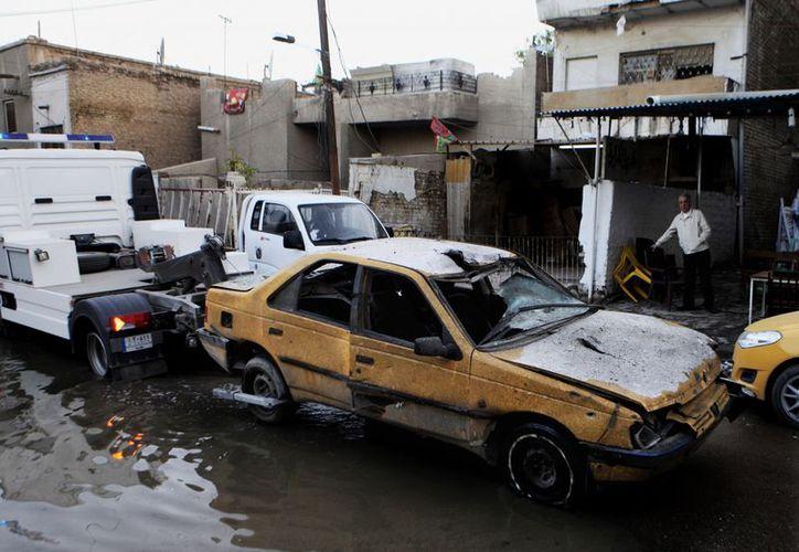 Fuerzas de seguridad remolcan un vehículo dañado por una explosión en el barrio chiíta de Karrada, en Bagdad, este lunes. (Agencias)