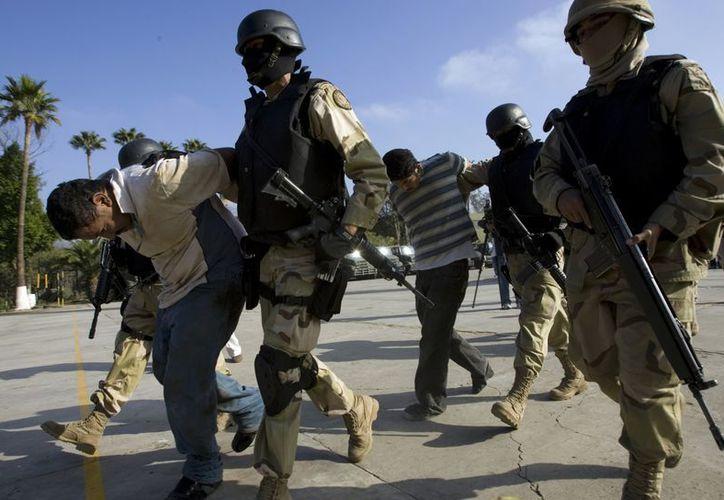 En esta foto del 3 de diciembre de 2008, efectivos del Ejército mexicano conducen a dos supuestos narcotraficantes hacia una prisión en Tijuana. (Agencias)