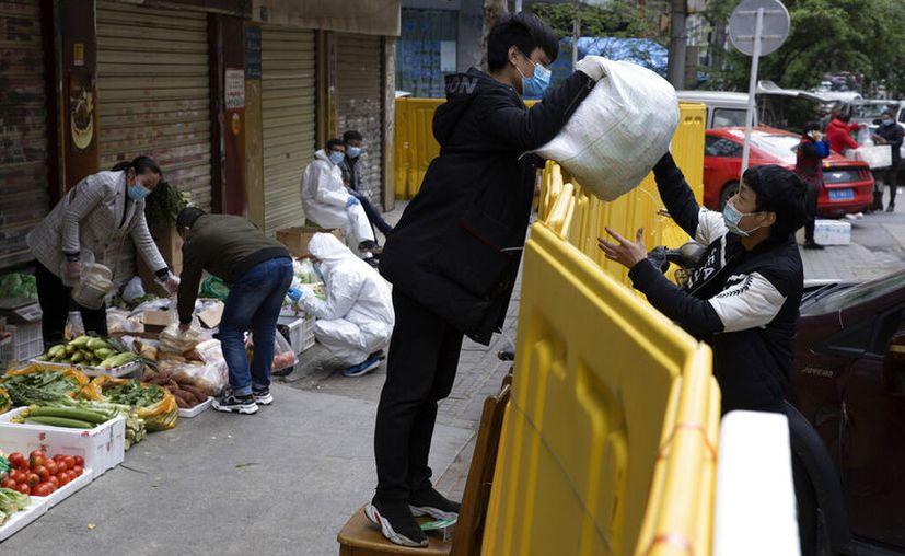 Un vendedor entrega una bolsa de alimentos a un cliente sobre una barrera que aísla un barrio para contener la propagación de COVID-19 en Wuhan, China, viernes 3 de abril de 2020.(AP Foto/Ng Han Guan)