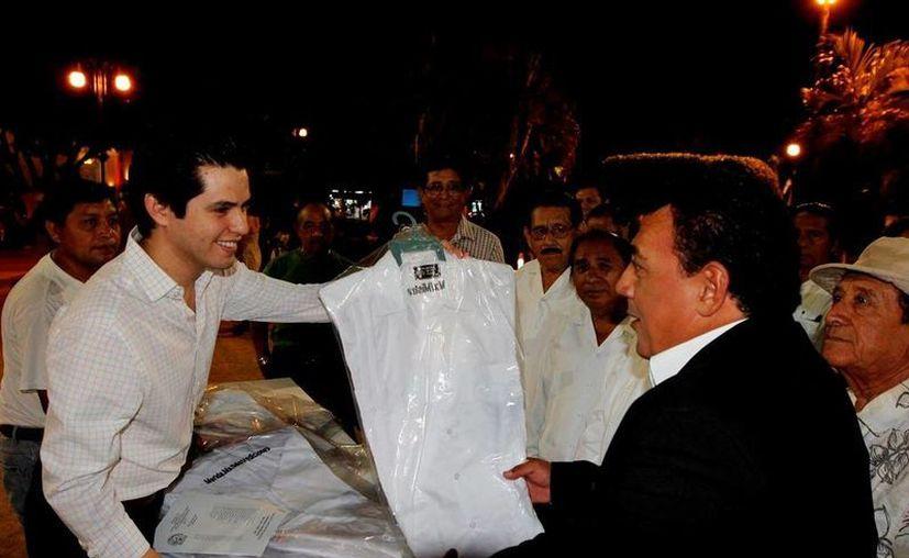 El regidor Luis Castillo López entrega una guayabera a uno de los trovadores de la Plaza Grande. (SIPSE)