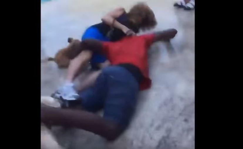 Entre gritos y burlas hacia la mujer, un sujeto se acerca, la toma por las piernas, la levanta y la tira al piso. (Foto: YouTube)
