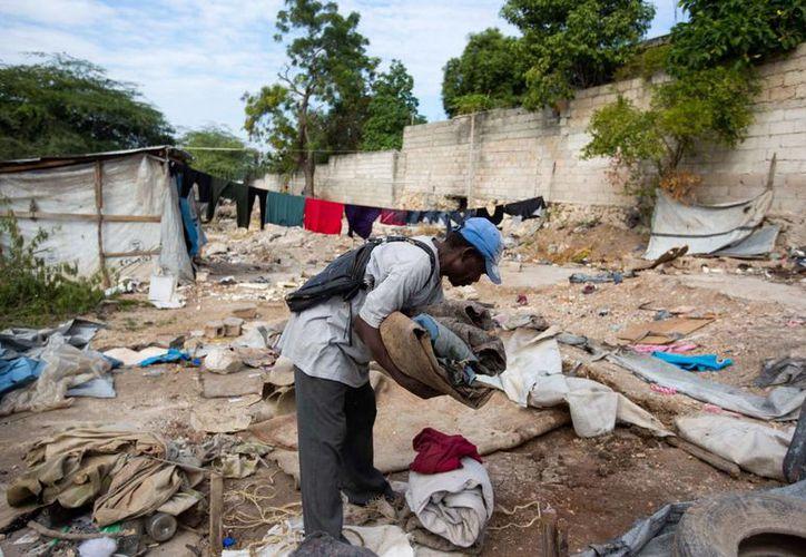 Un hombre recoge sus pertenencias fuera de su refugio en el campamento Delmas, instalado hace casi siete años para los damnificados del terremoto de 2010 en Puerto Príncipe. (AP/Dieu Nalio Chery)