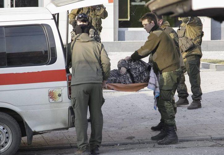 Separatistas prorrusos cargan el cuerpo de una víctima de un bombardeo en Donetsk, Ucrania. (EFE)
