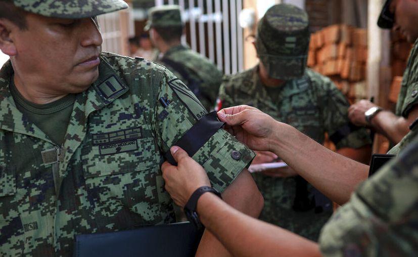 Foto: Un oficial del ejército mexicano recibe una cinta negra en la manga el sábado 19 de octubre de 2019 durante el funeral en Veracruz, México, de Alfredo González Muñoz, un soldado que murió en una intensa batalla en la ciudad de Culiacán entre hombres armados y fuerzas de seguridad. (AP Foto/Felix Márquez)