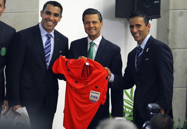 Tras pitar el Alemania 7-1 Brasil en la semifinal del Mundial, el árbitro mexicano Marco Rodríguez (i) fue felicitado por el presidente Enrique Peña Nieto. (Notimex)