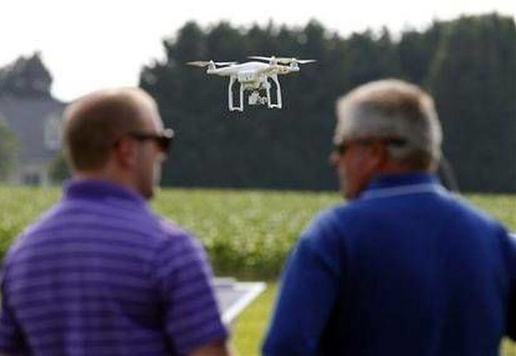 Imagen de Matthew Creger (izquierda), director de mercadotecnia de Intelligent UAS y Chip Bowling, presidente de la Asociaciión Nacional de Cultivadores de Maíz, durante una exhibición de drones en Cordova, Maryland. (Agencias)