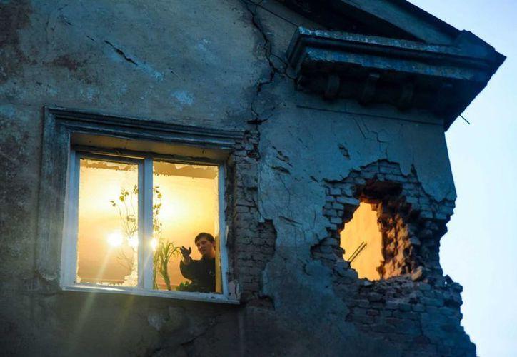 Un hombre observa los daños en vivienda tras el intercambio de proyectiles entre separatistas respaldados por Rusia y tropas del gobierno ucraniano en Donetsk, en el este de Ucrania. (AP)