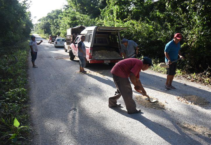 Habitantes de Felipe Carrillo Puerto tomaron la iniciativa de realizar trabajos de bacheo y chapeo de la vía.(Foto: Alejandro Poot/SIPSE)