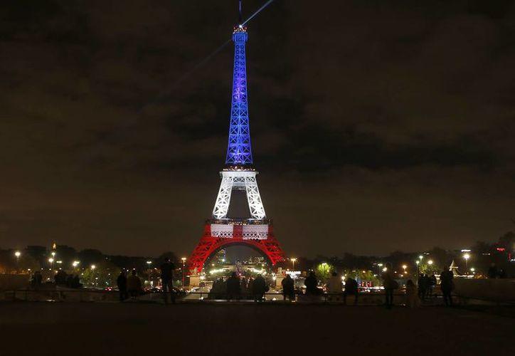 La Torre Eiffel se iluminó con los colores franceses en honor de las víctimas de los ataques del viernes en París, en el primero de tres días de luto. El día de hoy se realizó un minuto de silencio en memoria de las víctimas mortales. (AP Photo/Frank Augstein)