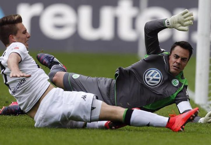 Patrick Herrmann (i), del Moenchengladbach, falla un gol ante el arquero suizo Diego Benaglio, de Wolfburg, que terminó por perder 1-0 y así dar el título de liga de forma indirecta a Bayern Munich. (Foto:AP)