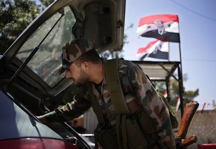 Un soldado sirio revisa el interior de un vehículo en un puesto de control en la calle Baghdad, en Damasco, Siria. (Agencias)