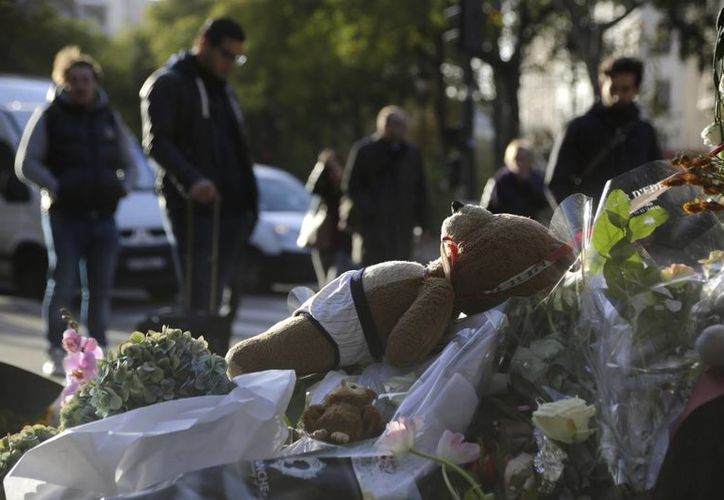 Juguetes, fotos, flores, velas y mensajes han sido colocados a las afueras de la sala de conciertos Bataclan en París, donde ocurrió uno de los atentados. (Agencias)